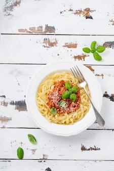 밝은 나무 배경에 흰색 접시에 볼로네제 소스, 바질, 파마산 치즈를 곁들인 전통 이탈리아 요리 페투치니 파스타. 평면도.
