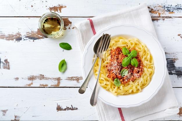 밝은 나무 배경에 흰색 접시에 그레고리력 소스, 바질, 파마산 치즈와 함께 전통적인 이탈리아 요리 페투치니 파스타