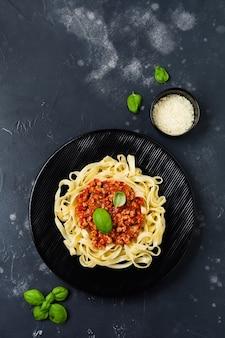 어두운 나무 배경에 검은 접시에 그레고리력 소스, 바질과 파르 메산 치즈와 함께 전통적인 이탈리아 요리 페투치니 파스타