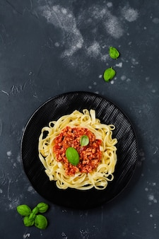 Traditional italian dish fettuccine pasta with bolognese sauce, basil and parmesan cheese in black plate on dark wooden surface. top view