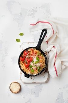 Традиционное итальянское блюдо из спагетти с томатным соусом и сыром пармезан в керамической тарелке на легкой бетонной поверхности. выборочный фокус. вид сверху.