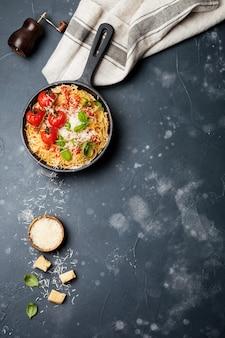 Традиционное итальянское блюдо из спагетти с томатным соусом и сыром пармезан в железной сковороде на темной старой бетонной поверхности. выборочный фокус. вид сверху.