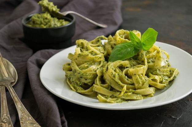 Traditional italian dish. pasta with pesto on black