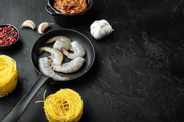 전통적인 이탈리아 요리입니다. 페스토 리코타 파마산 파스타와 구운 해산물 재료 세트, 검은 돌 배경, 텍스트 복사 공간