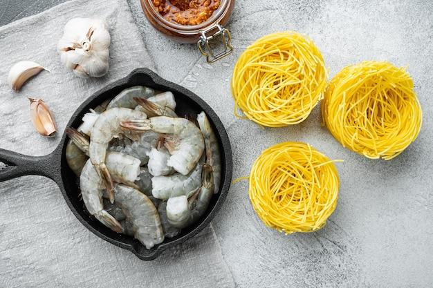 전통적인 이탈리아 요리. 페스토 리코 타 파마산 파스타와 구운 해산물 재료 세트, 회색 돌 테이블, 평면도 평면 누워