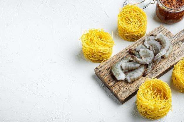 전통적인 이탈리아 요리. 페스토 리코 타 파마산 파스타와 구운 해산물 재료 세트, 흰 돌 표면에