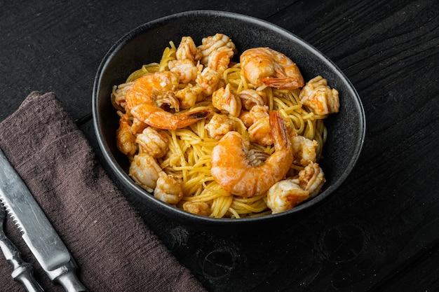 전통적인 이탈리아 요리. 파스타 리코 타 치즈와 구운 해산물 세트, 그릇에 검은 나무 테이블에 파스타