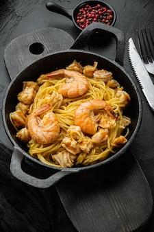 전통적인 이탈리아 요리. 페스토 리코 타 파마산 파스타와 구운 해산물 세트, 주철 프라이팬, 검은 돌 테이블에