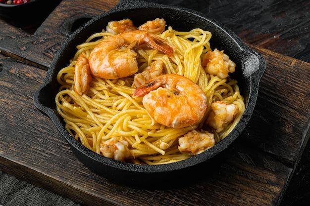 전통적인 이탈리아 요리. 페스토 리코 타 파마산 파스타와 구운 해산물 세트, 주철 프라이팬, 오래 된 어두운 나무 테이블에