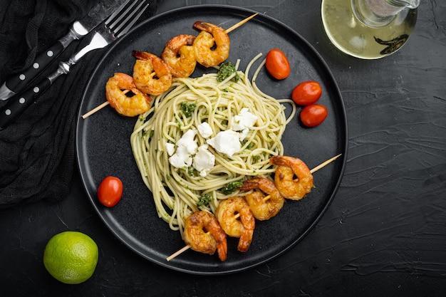전통적인 이탈리아 요리. 페스토 리코 타 파마산 파스타와 구운 해산물 세트, 접시, 검정