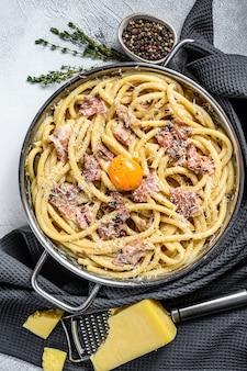 伝統的なイタリア料理のスパゲッティカルボナーラとフライパンのクリームソースのベーコン