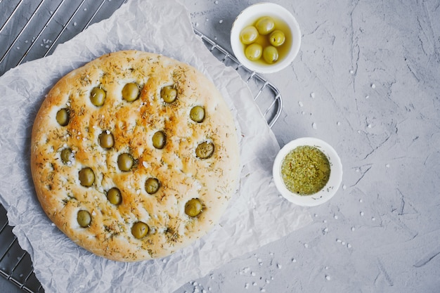 Traditional italian focaccia bread with olives, rosemary, salt and olive oil