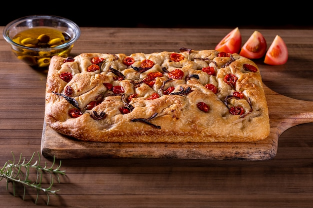 Traditional italian focaccia with cherry tomatoes, black olives and rosemary