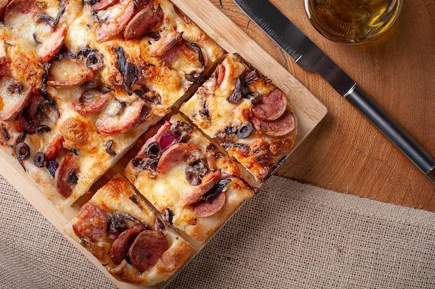 Традиционная итальянская фокачча с колбасой пепперони, маслинами, сыром пармезан и луком - домашняя лепешка фокачча. вид сверху