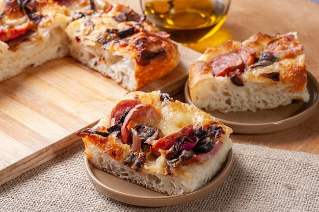 Традиционная итальянская фокачча с колбасой пепперони, маслинами, сыром пармезан и луком - домашняя лепешка фокачча.