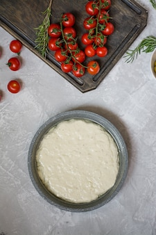 Traditional italian focaccia with tomatoes, olives and rosemary
