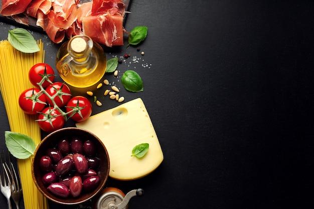 スパゲッティトマトチーズオリーブと暗い背景に油と伝統的なイタリア料理の背景。