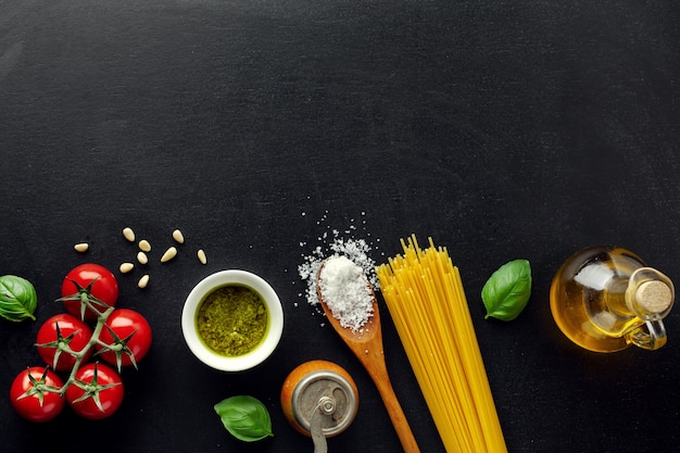 Traditional italian food background with spaghetti tomatoes cheese olives and oil on dark background.