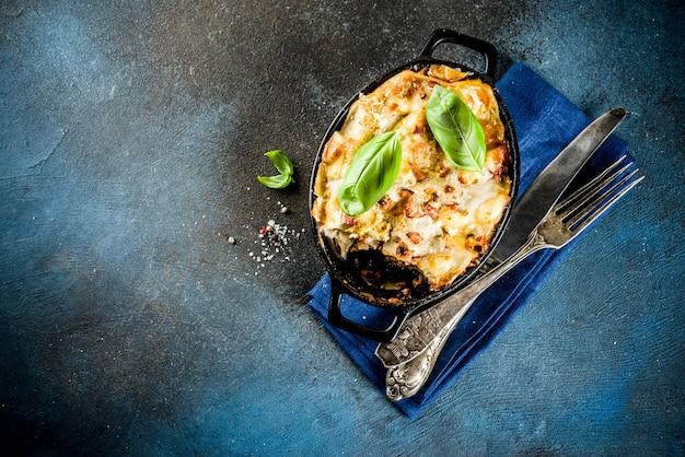 Traditional italian food, homemade lasagna with fresh basil, dark blue background