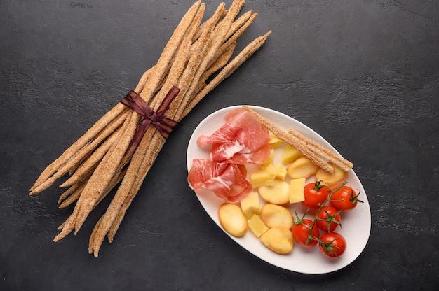 전통적인 이탈리아 음식은 어두운 배경에 접시에 퀴 토우 토, 치즈, 허브와 함께 토마토와 그리 시니 빵입니다.