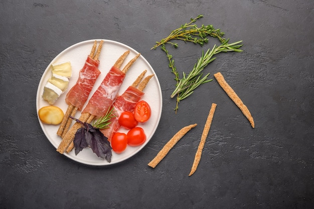Traditional italian food is grissini bread with prosciutto, cheese and tomatoes with herbs on a plate on a dark background.