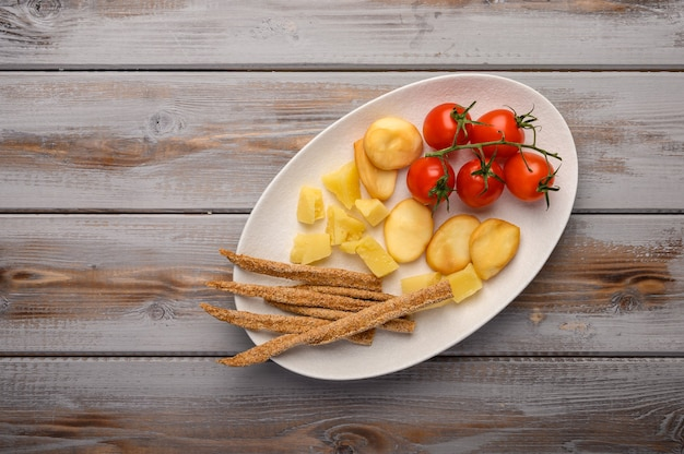 Traditional italian food is grissini bread with prosciutto, cheese and tomatoes with herbs on a plate on a dwooden background.