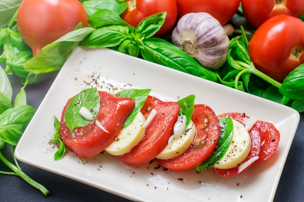 Traditional italian food, sliced tomatoes and mozzarella and basil on a white plate