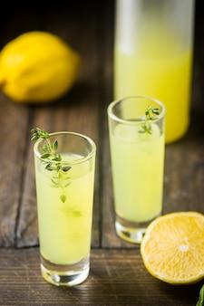 伝統的なイタリアのレモンリキュールリモンチェッロと新鮮な柑橘類のレモン。アルコール飲料。