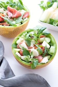 生ハムまたはハモン、モッツァレラチーズ、白いテーブルのメロンプレートにグリーンハーブを添えた伝統的なイタリア料理またはスペイン料理のサラダフレッシュメロン、上面図、軽い地中海料理料理、縦長の画像