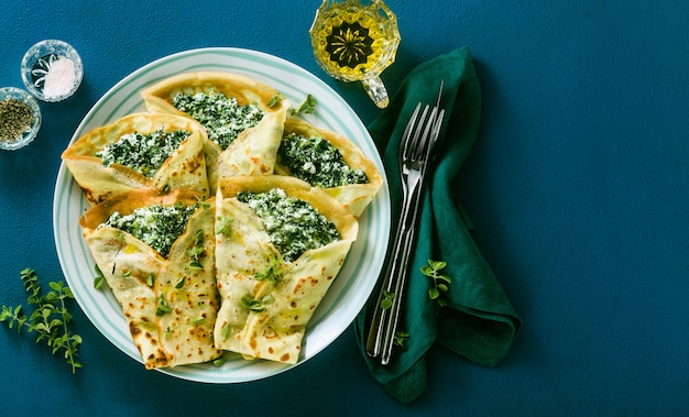 Традиционные итальянские блины блины со шпинатом и рикоттой на голубой стол подается. здоровая вегетарианская диета