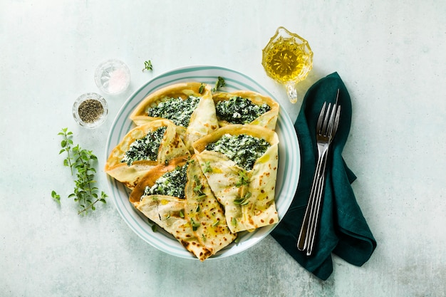 Традиционные итальянские блины блины со шпинатом и рикоттой на стол подается. здоровая вегетарианская диета