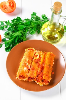 Traditional italian pasta cannelloni. baked tubes stuffed with minced meat