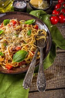 Традиционная итальянская паста маринара. классический рецепт римской кухни - паста букатини аматрикана с листьями базилика на деревянном деревенском фоне