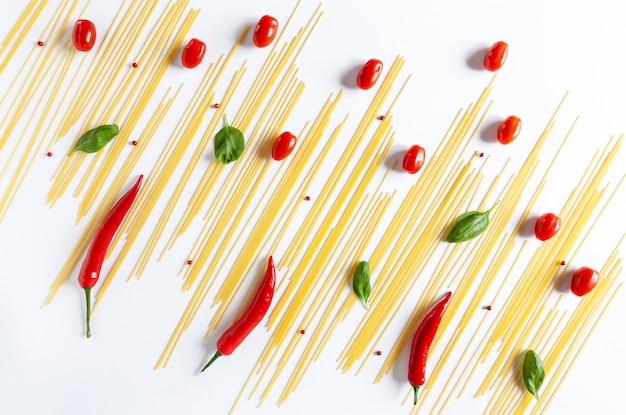 伝統的なイタリアのパスタスパゲッティ、チェリートマト、バジル、チリペッパー。上面図、クローズアップ、白い背景の上のコピースペース
