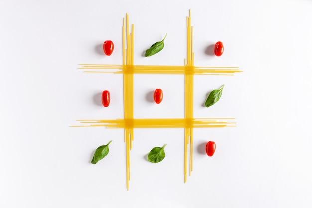 伝統的なイタリアのパスタスパゲッティ、チェリートマト、バジル。上面図、クローズアップ、白い背景の上のコピースペース