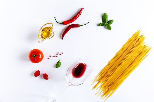 伝統的なイタリアのパスタスパゲッティ、トマト、バジル、オリーブオイル、唐辛子、赤ワインのグラス。上面図、クローズアップ、白い背景の上のコピースペース