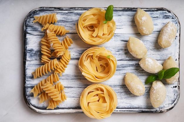 伝統的なイタリアのパスタ:バジルの葉で飾られたタリアテッレ、フジッリ、ニョッキ。イタリア料理のコンセプト。上面図。フラットレイ