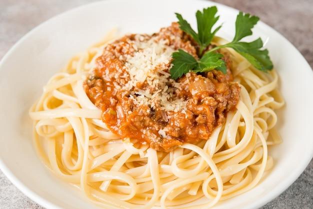 Традиционная итальянская паста с соусом болоньезе в белой тарелке, крупным планом