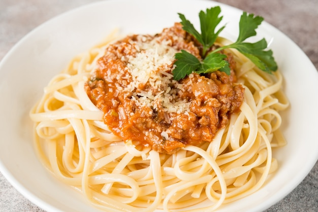 Traditional italian pasta with bolognese sauce in a white plate, close up