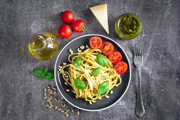 灰色の石の背景に黒いボウルに新鮮な野菜、パルメザンチーズ、バジルの葉、松の実、ペストソースを添えた伝統的なイタリアのパスタ。上面図、フラットレイ