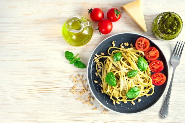 新鮮な野菜、パルメザンチーズ、バジルの葉、松の実、ペストソースを白い木製の背景に黒いプレートで添えた伝統的なイタリアンパスタ。上面図、フラットレイ、コピースペース。
