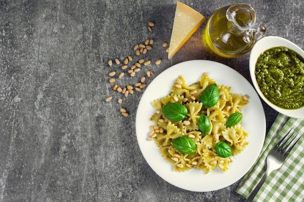 灰色の石の背景に白いプレートに新鮮な野菜、パルメザンチーズ、バジルの葉、松の実、ペストソースを添えた伝統的なイタリアのパスタ。上面図、フラットレイ、コピースペース。