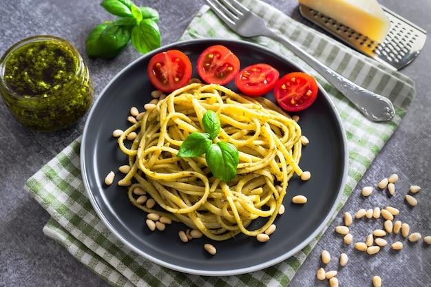新鮮な野菜、パルメザンチーズ、バジルの葉、松の実、ペストソースを添えた伝統的なイタリアンパスタ。灰色の石の背景に黒いプレートでお召し上がりいただけます。上面図、フラットレイ