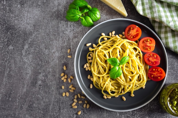 Traditional italian pasta with fresh vegetables, parmesan cheese, basil leaves, pine nuts and pesto sauce in black bowl on grey stone background. top view, flat lay, copy space.