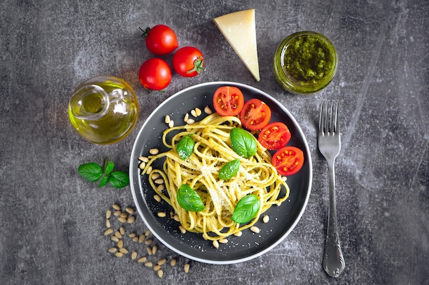 Traditional italian pasta with fresh vegetables, parmesan cheese, basil leaves, pine nuts and pesto sauce in black bowl on grey stone background. top view, flat lay