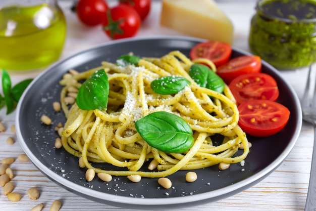 Traditional italian pasta with fresh vegetables, parmesan cheese, basil leaves, pine nuts and pesto sauce in black plate on white wooden background.