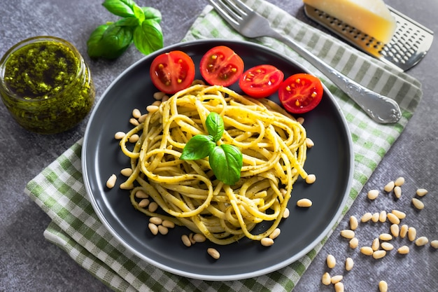 Traditional italian pasta with fresh vegetables, parmesan cheese, basil leaves, pine nuts and pesto sauce, served in black plate on grey stone background. top view, flat lay