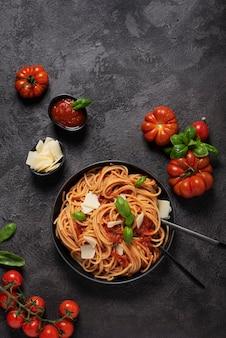 Традиционная итальянская паста с томатным соусом, базиликом и сыром на черном фоне, вид сверху вниз с копией пространства
