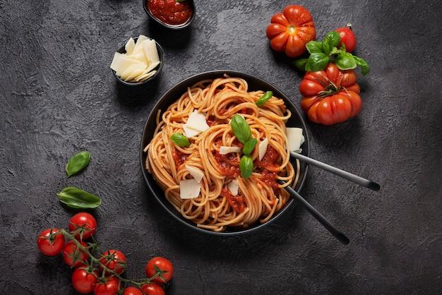 Традиционная итальянская паста с томатным соусом, базиликом и сыром на черном, вид сверху вниз с копией пространства