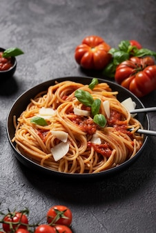Traditional italian pasta with tomato sauce, basil and cheese on the black background, top down view with copy space